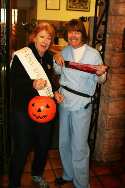 dorian emery left and longtime co worker michele mcclinton goof around during halloween at the aspen police department
