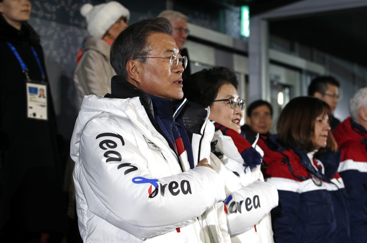 South Korean President Moon Jae-in, left, stands alongside first lady Kim Jung-sook as the South Korean national anthem is played at the opening ceremony of the 2018 Winter Olympics in Pyeongchang, South Korea, Friday, Feb. 9, 2018. (AP Photo/Patrick Semansky, Pool)