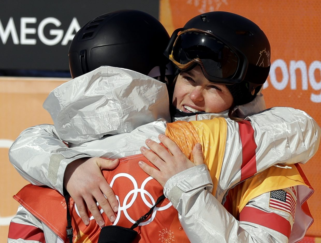Arielle Gold, right, of the United States,embraces Kelly Clark, of the United States, during the women's halfpipe finals at Phoenix Snow Park at the 2018 Winter Olympics in Pyeongchang, South Korea, Tuesday, Feb. 13, 2018. (AP Photo/Gregory Bull)