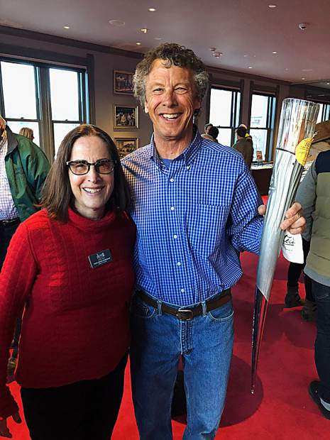 Aspen Historical Society Board VP Ruth Owens Hanrahan with her brother in law, Jim Hanrahan, holding an Olympic torch.