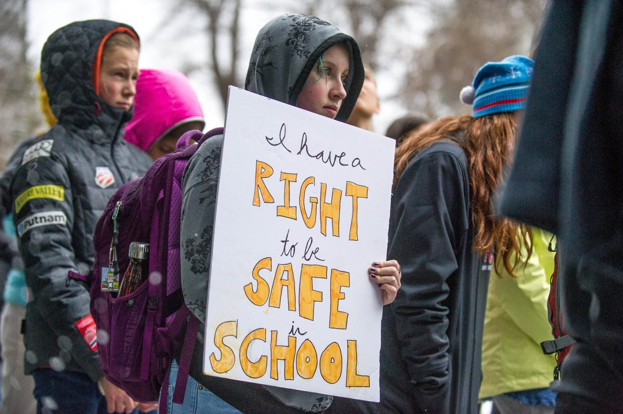 Aspen High School student Tilly Swanson, freshman, holding a sign at Paepcke Park on Friday for a student-organized walkout addressing all of the school shootings.