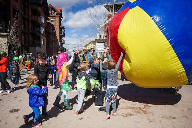 Kids push a giant beach ball around base village on Saturday for part of the closing festivities at Snowmass.
