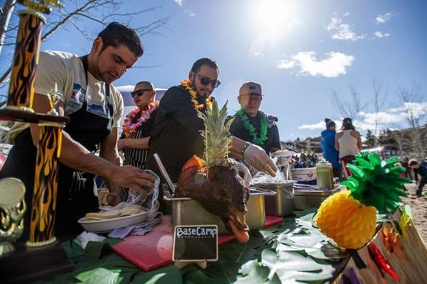 Chefs get ingredients for the pig roast at Base Village in Snowmass on Saturday for closing weekend.