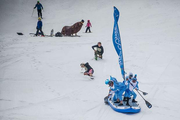 The Shaboomee Snow Sharks make their way to the pond skim for Schneetag at Snowmass on their oversized stand up paddle board on Sunday.