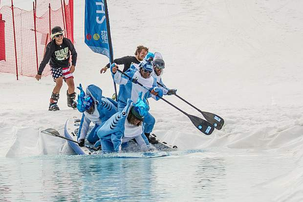 The Shaboomee Snow Sharks enter the pond skim for Schneetag at Snowmass on their oversized stand up paddle board on Sunday.