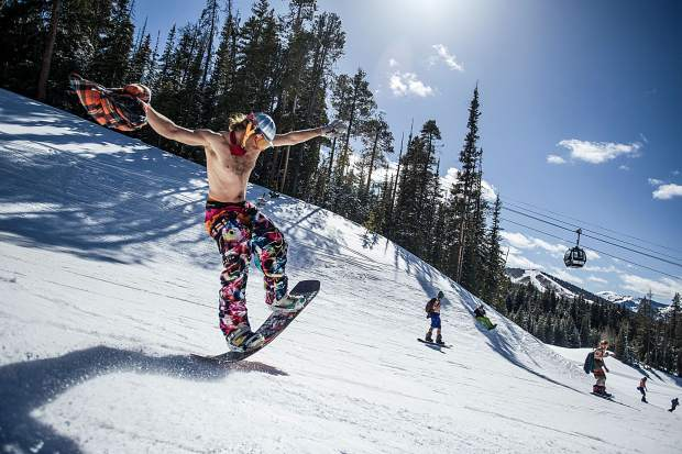 A snowboarder butters on the swimsuit ski down on Adam's Avenue at Snowmass on Saturday for closing festitivites.