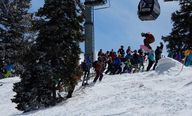 A crowd cheers as a rider catches air on Boyd's Bump on the Ridge of Bell Sunday for closing day on Aspen Mountain.