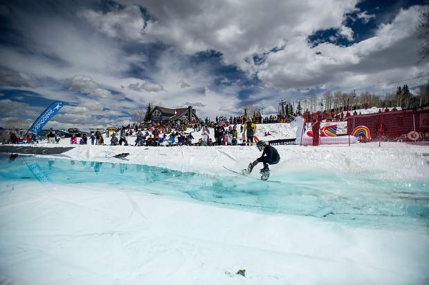 Jim Callen snowboards across the pond skim at Snowmass for closing weekend on Sunday.
