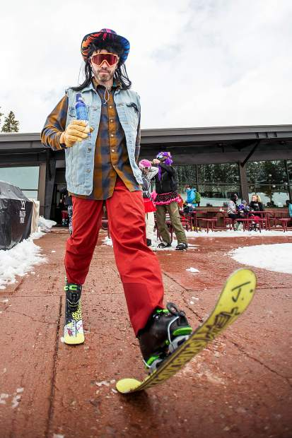 Damian Quigley walks in his snow blades outside of the Merry Go Round Restaurant on Sunday for closing day at Aspen Highlands.