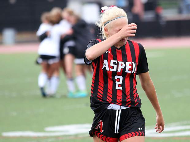 Aspen senior Maddy Bergdahl wipes tears from her eyes as the Jefferson Academy girls soccer team celebrates its 1-0 win over the Skiers in Saturday's 3A state semifinal game at All-City Stadium in Denver.