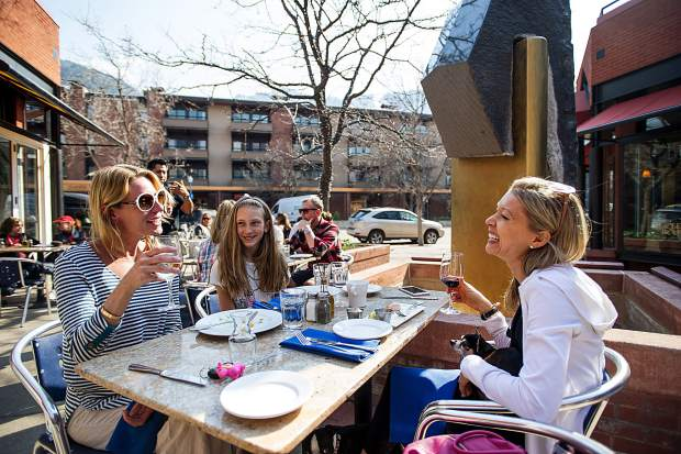 Jess Ewart, left, enjoys a glass of wine with her friend Jen Carter and a meal with her daughter Zoe Ewart-Adams on the terrace of Mezzaluna in Aspen on Friday afternoon.