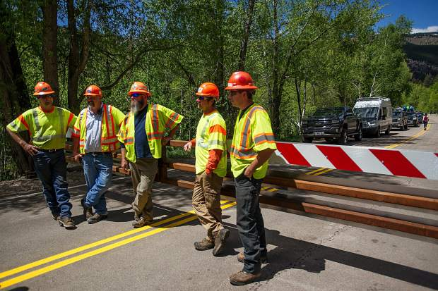 Colorado Department of Transportation workers hang by the gate on Independence Pass Road on Thursday before officially opening the gate at noon for car traffic for the summer season.