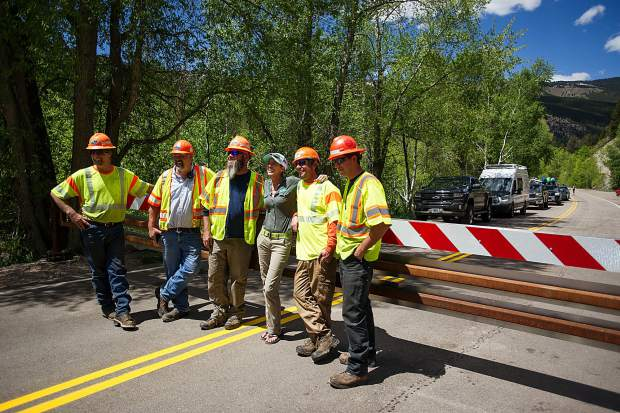 Colorado Department of Transportation workers and Independence Pass Foundation Executive Director Karin Teague hang by the gate on Independence Pass Road on Thursday before officially opening the gate at noon for car traffic for the summer season.