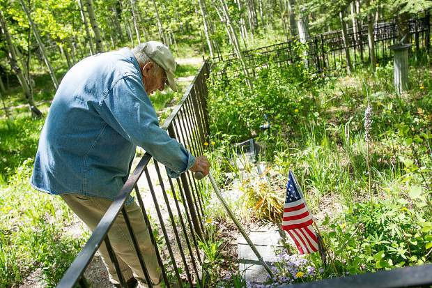 Aspen Grove Cemetery sexton Jim Markalunas clears off flowers with his cane to see the name on U.S. Army Captain Melvin Johnson's headstone Thursday morning.