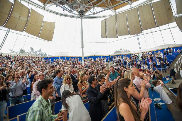 Audience members stand as the 2018 graduating class enters the Benedict Music Tent for the Aspen High School graduation ceremony on Saturday.