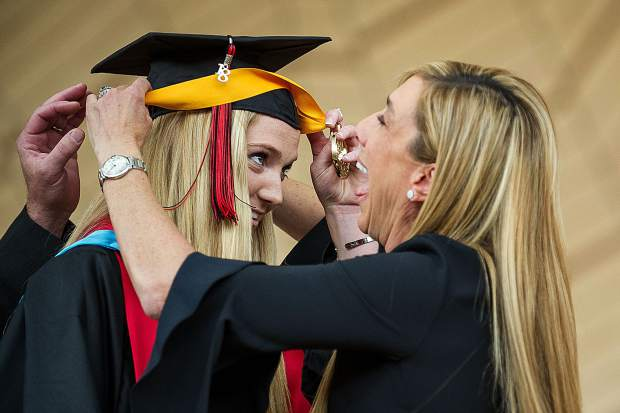 Aspen senior Sydney Forster's mom struggles to get the medal around her daughter's hat on stage before she gave her salutatory address for the Aspen High School graduation on Saturday at the Benedict Music Tent.
