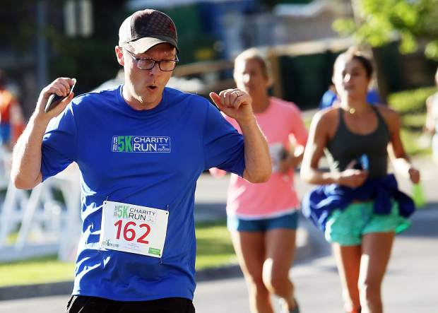 New Hampshire's Patrick McCusker celebrates as he crosses the finish line of the Food & Wine Celebrity Chef 5K Charity Run on Friday at Rio Grande Park in Aspen.