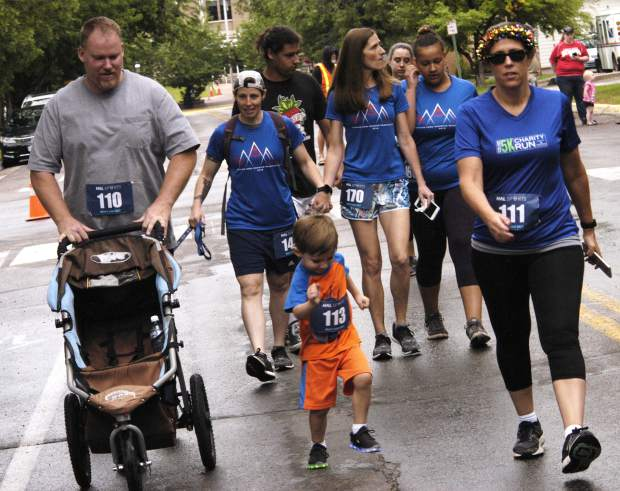 Bobby Hirons, pushing the empty stroller, his son, Peyton, running his first-ever 5K, and mom Cheryl, right, were among the many families taking in the annual Strawberry Shortcut for Father's Day on Sunday.