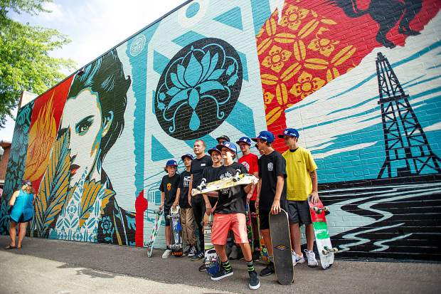 Artist Shepard Fairey poses for a photo with local youth skateboarders before the unveiling of his mural,