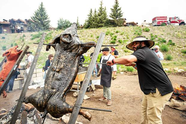 Mina Boules of the Venga Venga team paints an ash marinade on a pig roasting over an open fire at the Heritage Fire event in Snowmass on Saturday.