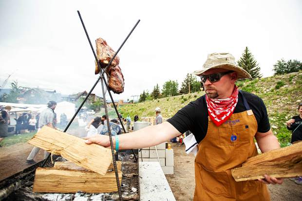 CEO of Stem Ciders and Acreage out of Lafayette, Eric Foster replaces wood on their fire roasting a lamb's head and vegetables at the Heritage Fire event in Snowmass on Saturday.