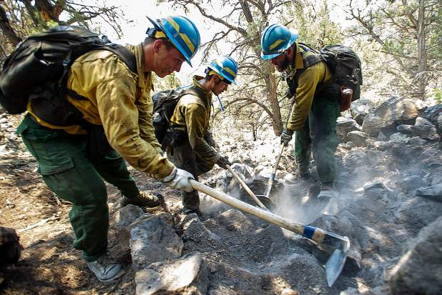 From left, firefighters Martin Sierra, Ismael Corona, and Martin Sierra put out hot spots above the Wilds neighborhood in Basalt from the Lake Christine Fire on Sunday afternoon.