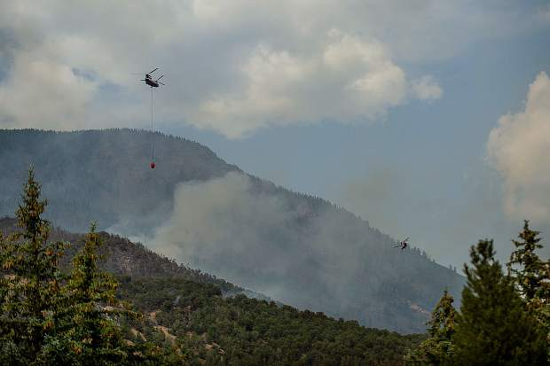 Helicopters carry buckets of water it gathered from Lake Christine on Basalt Mountain on Friday afternoon, July 6, for the Lake Christine fire.
