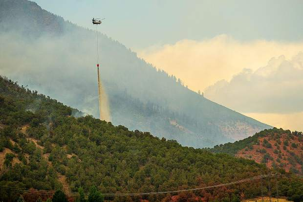 A huey helicopter drops a bucket of water it gathered from Lake Christine on Basalt Mountain on Friday afternoon, July 6, for the Lake Christine fire.