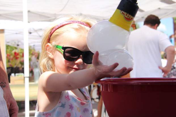 A young girl reaches out to hold some carbon dioxide soap bubbles at the Aspen Science Center's booth at a recent Aspen Saturday Market.