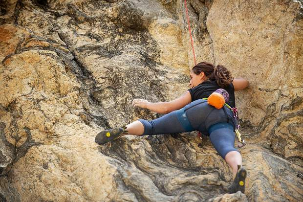 Catherine Davis makes a move rock climbing on the Grottos wall on Independence Pass on Saturday.