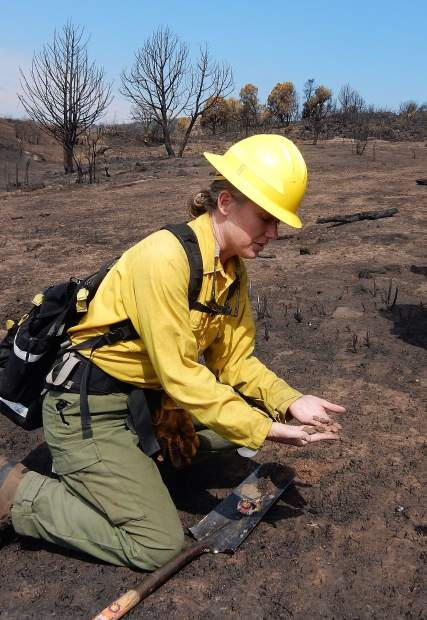 Hydrologist Beth Anderson shows conditions of soils in the Lake Christine Fire burn area on Saturday.