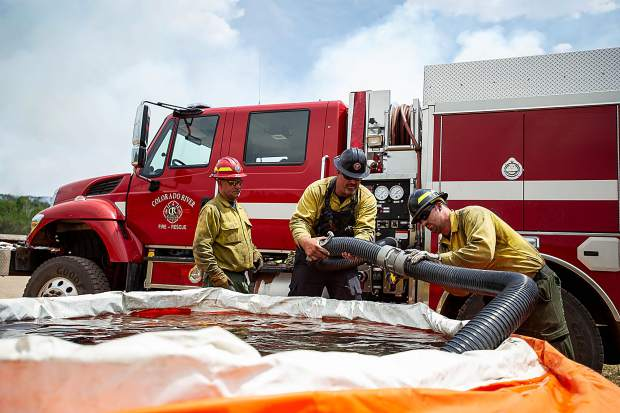 Colorado River Fire and Rescue crew members Kenny Hutchinson, right, Robert Cooney, center, and Jesse Sloan hook up an engine hose to gather water from the pumpkin at Drop Point 15 off of Cattle Creek Drive on Friday afternoon.