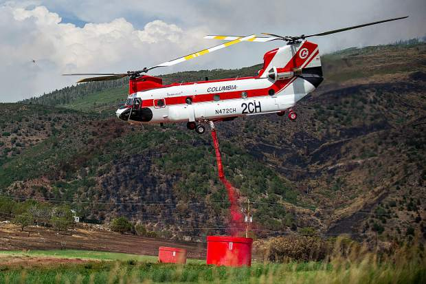 A chinook helicopter fills up with fire retardent to make a drop on the Lake Christine Fire at a pick up zone in Missouri Heights on Friday.