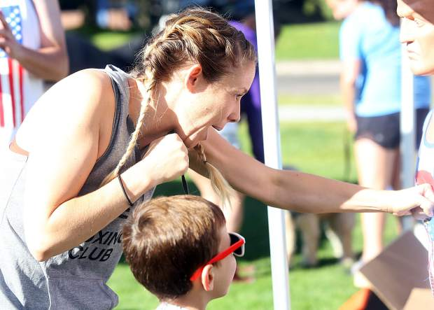 Arielle Gallagher of Lace Up Boxing shows a child how to punch at their tent Wednesday during the 32nd annual Boogie's Buddy Race at Rio Grande Park in Aspen.
