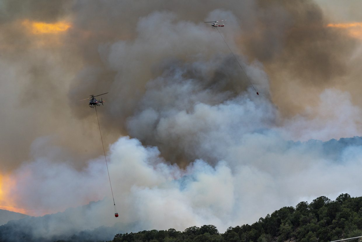 Helicopters dump water on the Lake Christine Fire Tuesday evening. They dipped their buckets into the Roaring Fork River and made repeated passes until dark. (Peter McBride / courtesy photo)