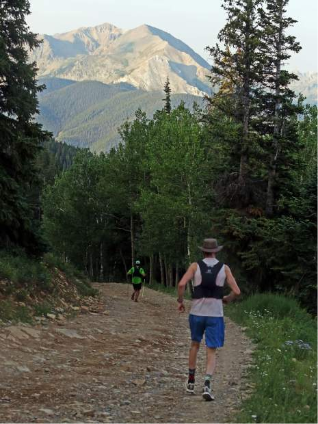 Trey Barnes, rear, makes his way down the backside of Aspen Mountain during the Power of Four trail run on Sunday, July 29, 2018. (Photo by Austin Colbert/The Aspen Times).