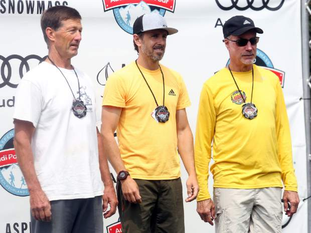 From left, Dave Peters, winner Cory Smith and David Butler stand on the men's Power of Four 10k trail run podium on Sunday, July 29, 2018. (Photo by Austin Colbert/The Aspen Times).