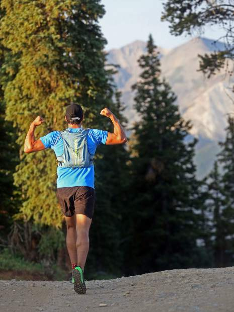 A racer flexes his biceps after cresting Aspen Mountain during the Power of Four 50k trail run on Sunday, July 29, 2018. (Photo by Austin Colbert/The Aspen Times).