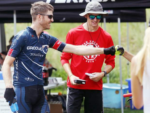 Race winner Thomas Herman gets a fist bump after finishing the Power of Four mountain bike race on Saturday, July 28, 2018. (Photo by Austin Colbert/The Aspen Times).