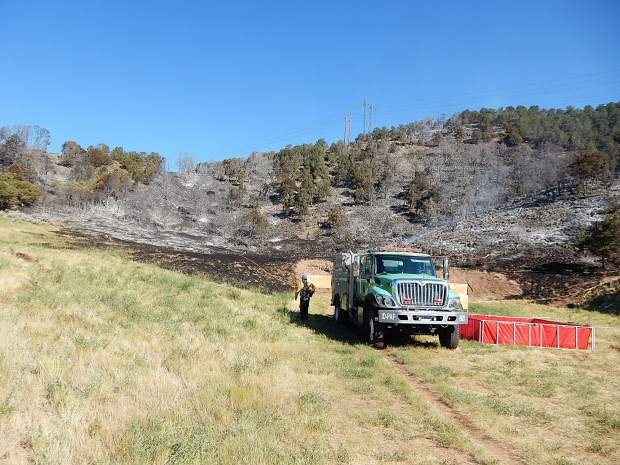 A U.S. Forest Service brush truck works Wednesday morning at the point of origin of the Lake Christine Fire. Illegal tracer rounds were fired from a gun and missed the cleared dirt area in the background. The fire started in the brush alongside the range.