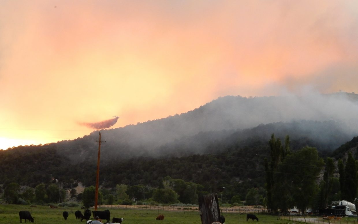 A fixed-wing plane makes a slurry drop Tuesday evening on the Lake Christine Fire near Basalt.