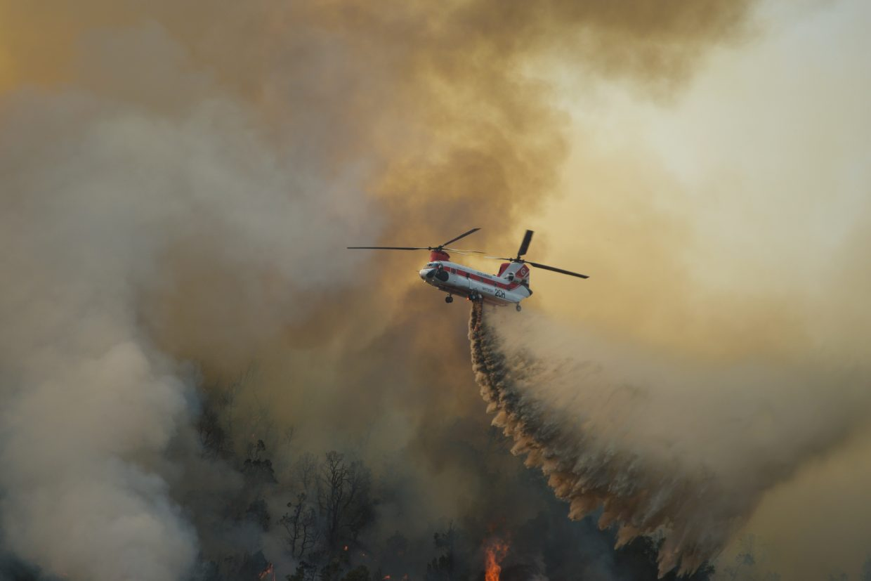 A helicopter drops water on the lower slopes of Basalt Mountain at about 7 p.m. Wednesday. Fire officials said an estimated 500 homes are threatened by the Lake Christine Fire.