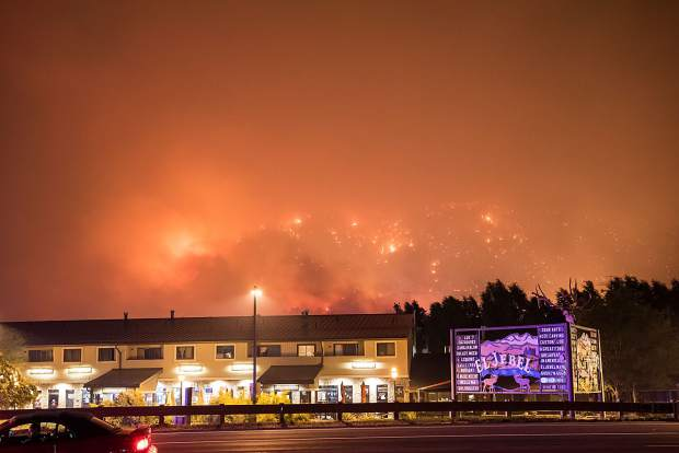 Looking across Highway 82 toward El Jebel, the night sky turns orange from the Lake Christine fire after the winds shift, forcing additional evacuations in the area on Wednesday, July 4, in El Jebel.