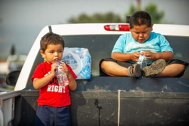 Eduardo Herrera, 7, and his brother Daniel, 2, sit in a parking lot in El Jebel after being evacuated from their mobile home Wednesday night from the Lake Christine fire.