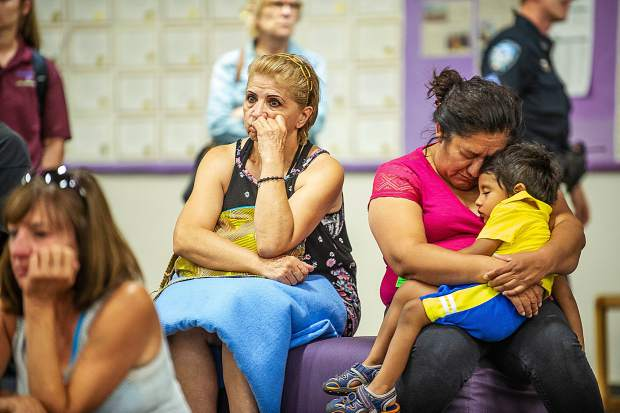 Celia Corona and her son Marco embrace and sleep after a long night from evacuating El Jebel on Thursday night from the Lake Christine fire at the community meeting with several other exhausted and discouraged evacuees at the Basalt High School.