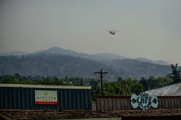 A helicopter flies over Basalt to dump water on the Lake Christine fire on Thursday.