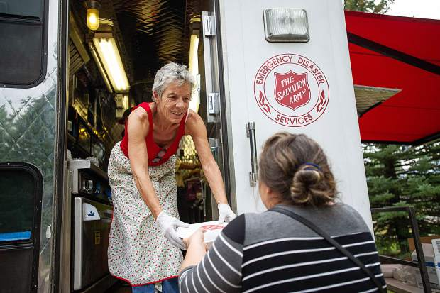 Volunteer Sara Fisher hands a meal to an evacuee of the Lake Christine fire Thursday evening in El Jebel from a Salvation Army truck. Fisher was previously a county commissioner in Pitkin County.