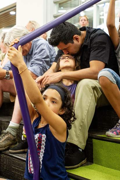 A father kisses his daughter on the head during the community meeting at the Basalt High School on Thursday evening regarding the Lake Christine fire.