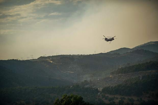 A helicopter fills up with water to make a drop on Basalt Mountain for the Lake Christine fire on Thursday, July 5.