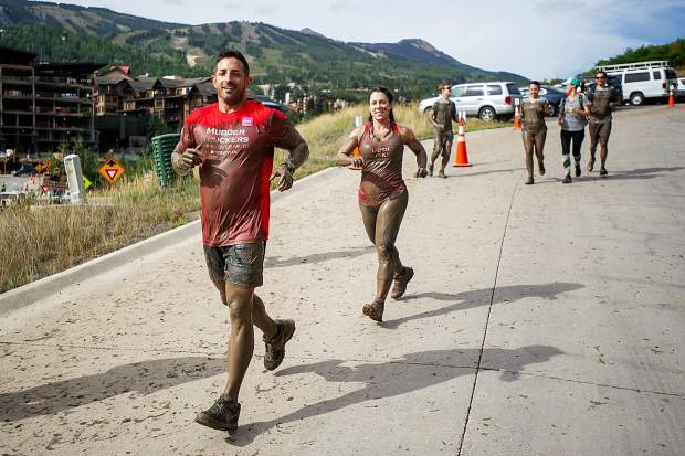 Tough Mudder participants run past Snowmass Town Hall.